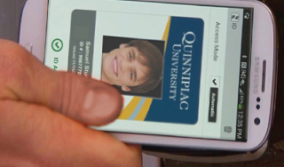 A picture of a hand clutching an old Android powered mobile handset. The display reads Quinnipiac University