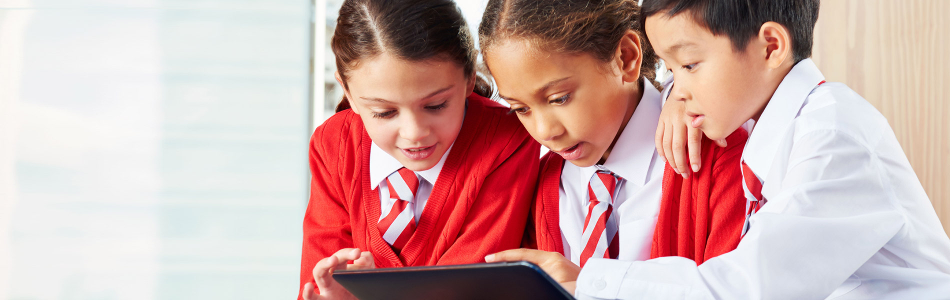 Image of three children using a Windows tablet in school
