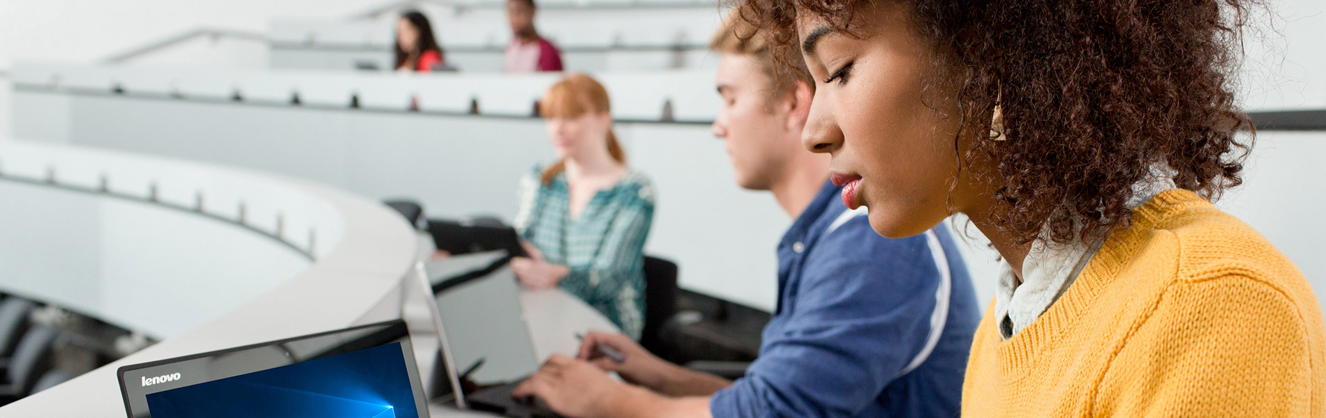A photograph of five students in a lecture hall, each sitting at a computer taking notes