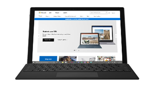 Photograph of a laptop displaying the Microsoft website.
