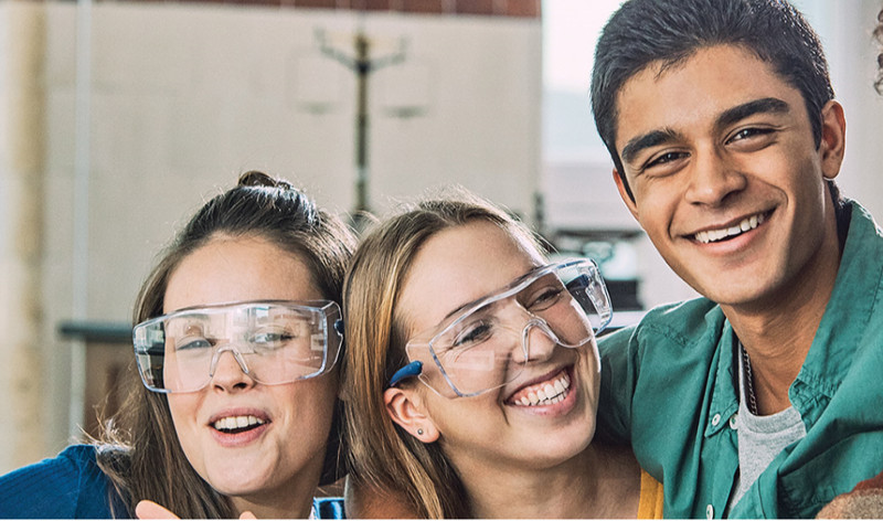 Four students with their arms round each other smiling, three of them are wearing safety goggles.