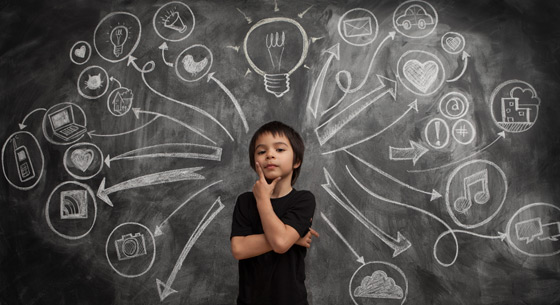 Image of a young boy with his hand on his chin thinking, in front of a chalkboard with thought bubbles coming out from behind him