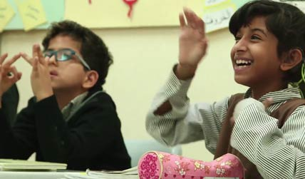 Two deaf children in a classroom using sign language click to open video popup