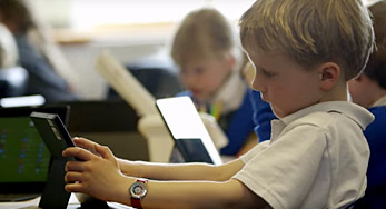 Click on this Image of a young blonde boy using a Microsoft surface in a classroom to watch a video about Broadclyst School, Devon