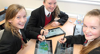 click on this Image of three girls using tablets for school work at Calaiste Bhaile Chlair school to view their showcase story