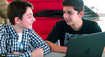 Click on this Image of two students collaborating on an important project with a laptop to watch a video from Doukas School, Greece