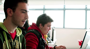 Click on this Image of two students studying hard in a classroom to watch a video about the Hellenic American Educational Foundation