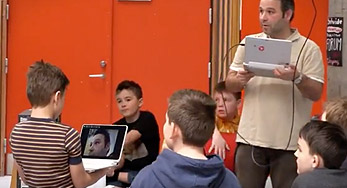 click on this Image of a teacher and students using computers in a lesson to watch a video about Hellerup School
