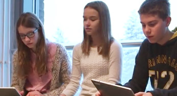 click on this Image of a trio of students using tablets to watch a video about Metsokangas School