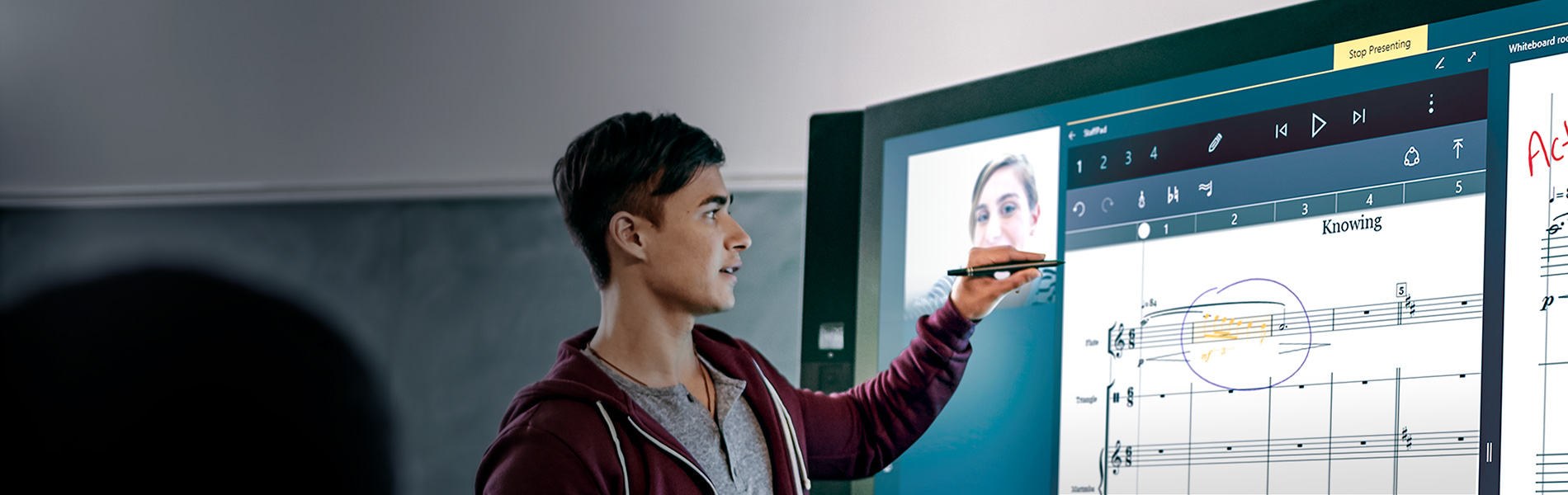 Picture of a man interacting with skype on a large monitor.
