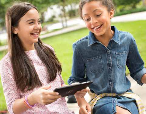 Two children smiling using one Surface outside in a park